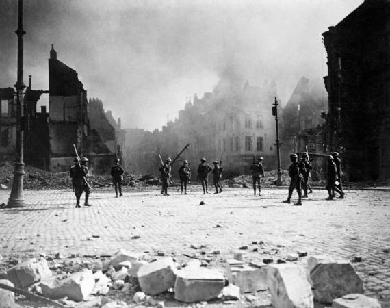 A group of Canadian soldiers strung out in the streets of Cambrai against its still burning buildings