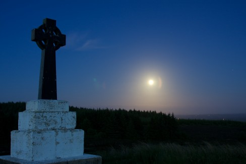 The moon glows brightly in the night sky near Bragan Penal Cross, Co. Monaghan