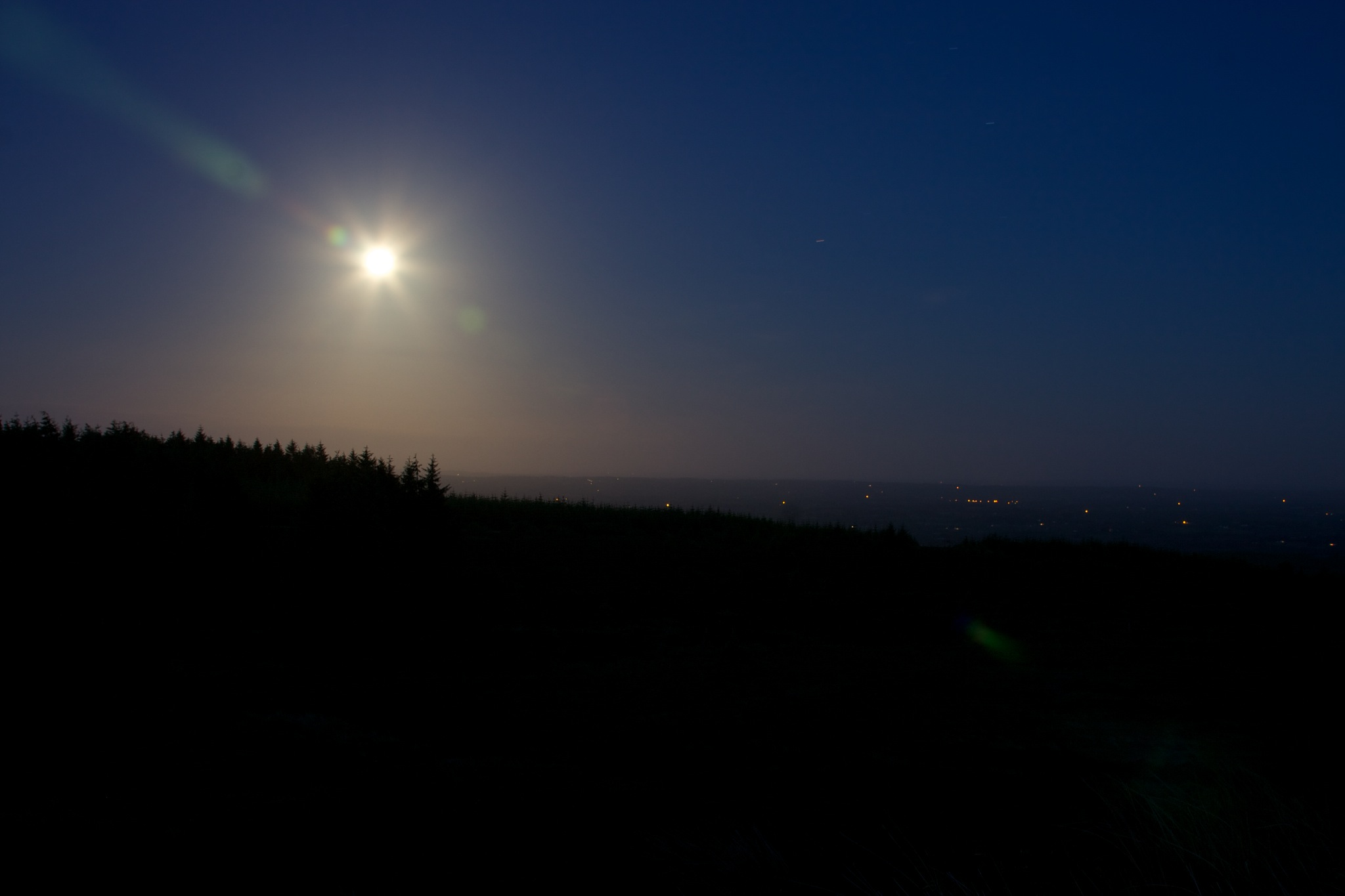 Bright hazy glow of the moon with the lights Monaghan town in the distance