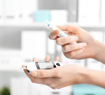 Woman holding digital glucometer and lancet pen on blurred background. Diabetes monitoring