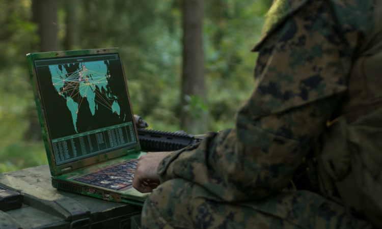 Military Operation in Action, Soldiers Using Military Grade Laptop Use Military Industrial Complex Hardware for Accomplishing International Mission. In the Background Camouflaged Tent on the Forest.