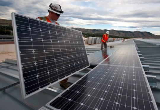 two workers installing solar panels