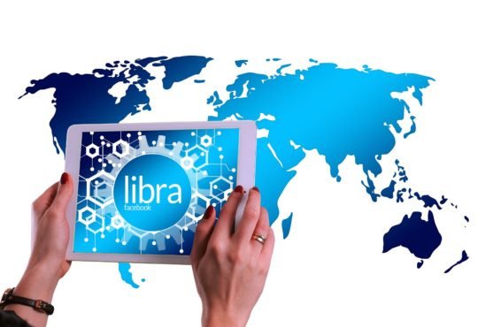 Hands holding a tablet with Libra on the screen with world map in background