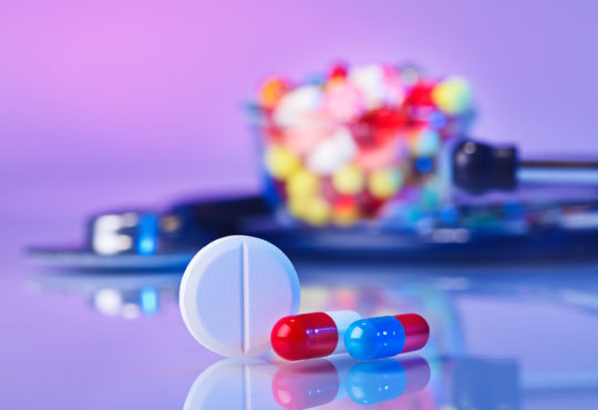 Pills and tablets macro still life on violet, medical therapeutic concept