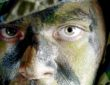 young soldier face with jungle camouflage paint