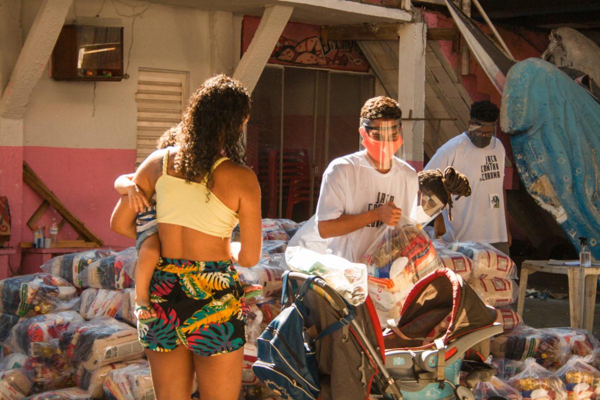 A mother and her baby receive humanitarian aid in the Jacarezinho favela, Rio de Janeiro.