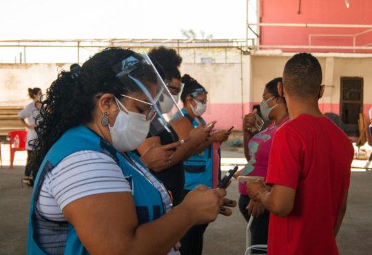 Reporters take down a resident's data in the Jacarezinho favela, Rio de Janeiro.